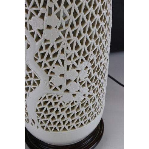 58 - A large oriental ceramic table lamp in reticulated and baluster form, with cherry blossom decoration...