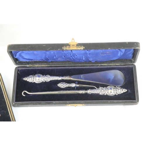 182 - Two Edwardian silver handled button hooks and a matching silver handled shoe horn, repousse foliate ...