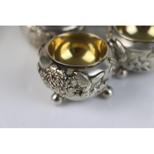 253 - A set of six oriental decorative white metal (tests silver) salts with gilt interior.