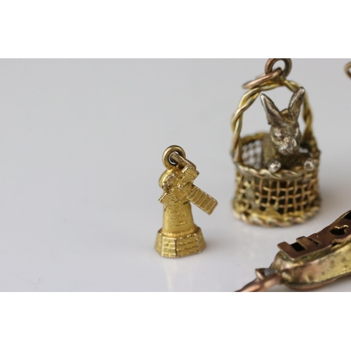 133 - Two 9ct gold charms, a 9ct gold and silver charm and a yellow metal charm (4) (af)