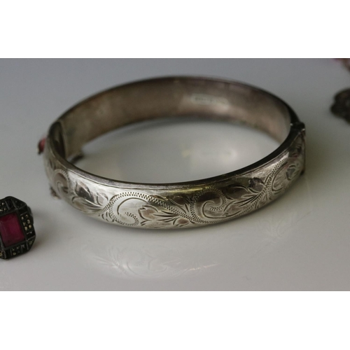 173 - Silver hinged bangle, bright cut floral repeating pattern, tongue clasp with safety chain, width app...