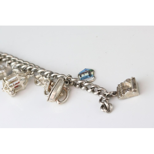 175 - Silver curb link charm bracelet with eighteen silver and white metal charms, length approx 23cm (rep...