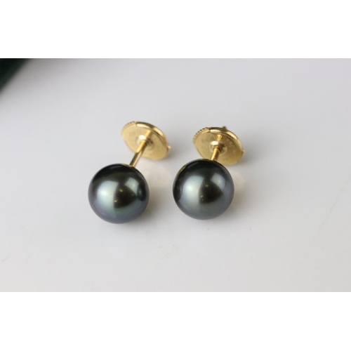 113 - Black pearl 18ct yellow gold stud earrings, the spherical black pearls with green lustre, diameter a...