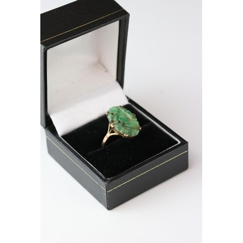 128 - Carved jade 9ct yellow gold ring, the oval pierced carved jade measuring approx 18mm x 11.5mm, claw ...