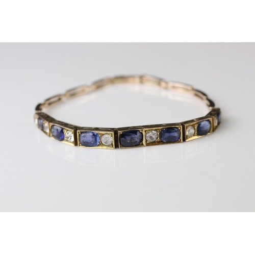 147 - Early 20th century sapphire and paste rose metal bracelet, seven graduated oval blue sapphires, the ...
