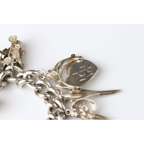 171 - Silver curb link charm bracelet with padlock clasp and sixteen silver and white metal charms