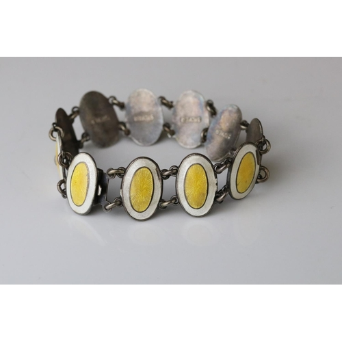 28 - Early 20th century enamelled silver panel bracelet, eleven oval yellow and white enamelled panels, c...