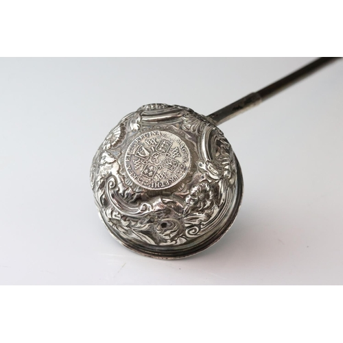 166 - White metal toddy ladle set with William and Mary coin to centre, repousse floral and foliate scroll...