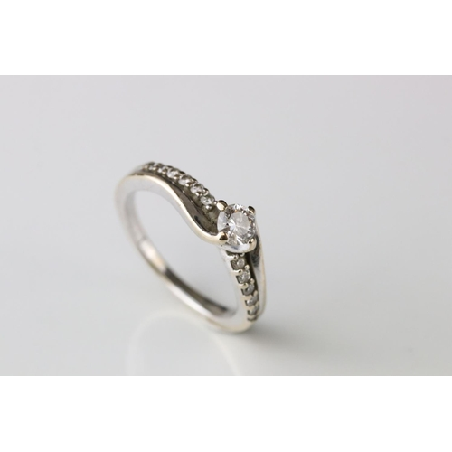 19 - Diamond 18ct white gold crossover ring, the principle round brilliant cut diamond weighing approx 0....