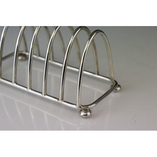 192 - George V silver seven bar toast rack of arched form raised on four bun feet with trefoil finial, mak...