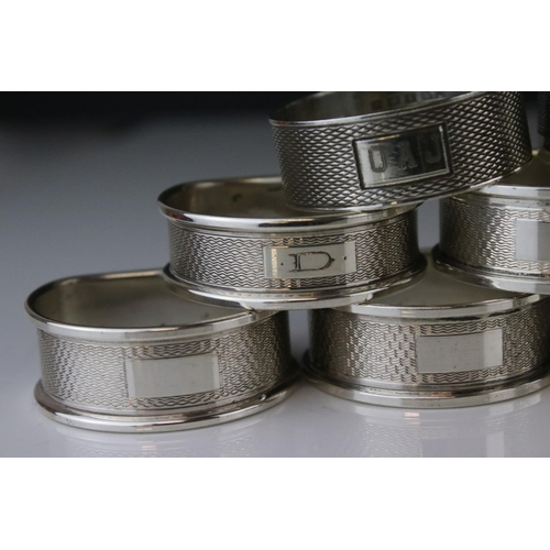 197 - Nine silver napkin rings to include a set of five, engine turned decoration, blank rectangular carto...