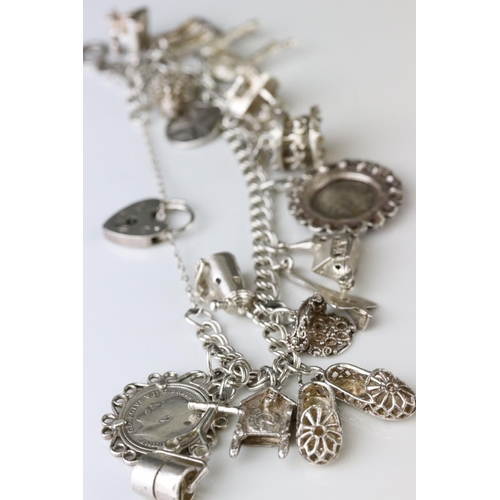 80 - Silver double curb link charm bracelet with padlock clasp and safety chain, eighteen silver and whit...