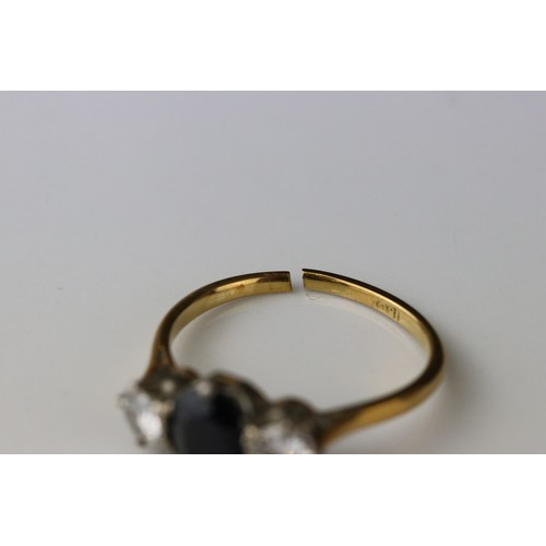34 - Sapphire and diamond three stone 18ct yellow gold platinum set ring, the oval mixed cut blue-black s...