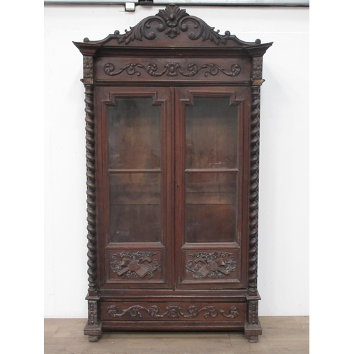 25 - A Continental carved oak glazed Bookcase....