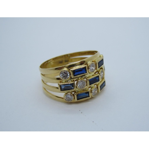 195 - A Dress Ring set blue and white stones to split shank in 18ct gold, ring size K, approx 3.20 gms....
