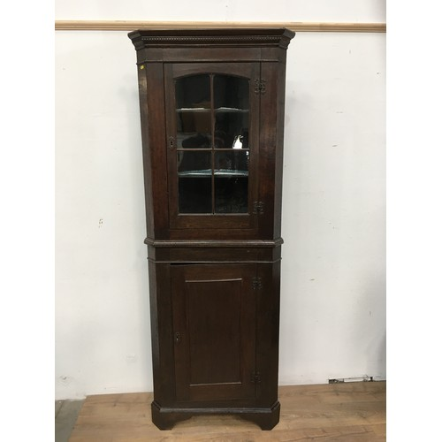 59 - A 19th Century oak standing Corner Cabinet the upper section fitted single glazed door above base fi...