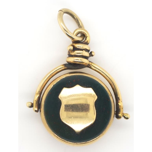 9 - 9ct gold fob spinner set with onyx and bloodstone. Mounted with a renaissance shield cartouche which...
