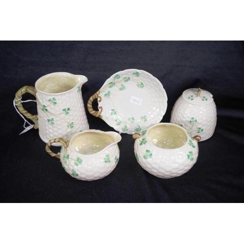 1056 - Five pieces Belleek tableware including cream jug, milk jug, sugar bowl, lidded honey pot, and a but...