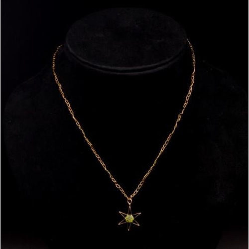 107 - A gold star pendant and gold chain set with a single peridot, marked 9ct to pendant bail and 585 to ...
