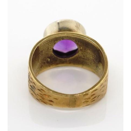 179 - 14ct yellow gold and amethyst ring with textured shoulders and a buff top cut amethyst. Marked 585. ...