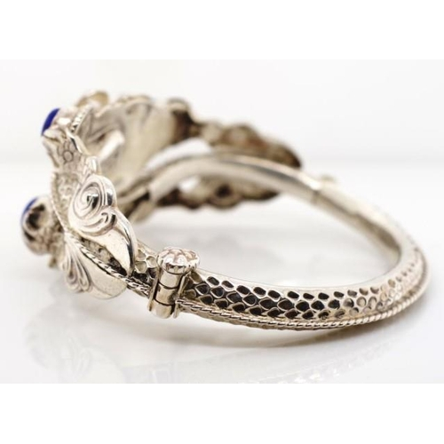304 - Silver dragon bangle set with blue hard stone. Approx 36 grams weight, 56mm width....