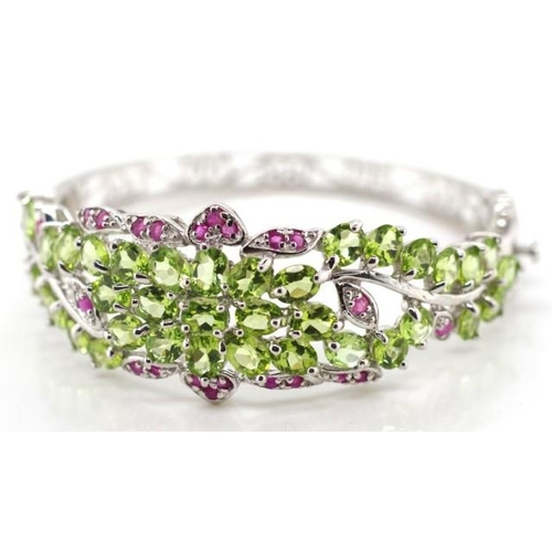311 - Peridot, ruby and sterling silver bangle with flower and scroll work decoration. Approx width 55mm...