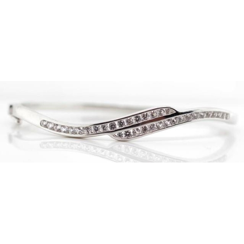 316 - Sterling silver bangle channel set with gemstones that test as white topaz.. Marked 925. With box cl...