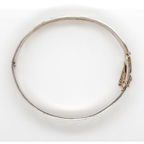 317 - Elizabeth II sterling silver bangle marked Birmingham MM 1973. With a hinge mechanism. Approx weight...