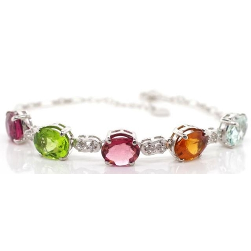 318 - Aquamarine peridot and tourmaline silver bracelet. Marked 925 approx 8.4mm x 7.2mm oval cut coloured...