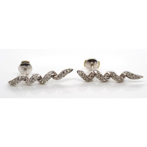 87 - 18ct white gold and diamond cluster earrings of spiral form with grain set round brilliant cut white...