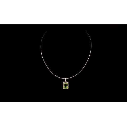 55 - 2.30ct Peridot, diamond and 18ct gold pendant and omega chain. The white gold setting and chain are ...