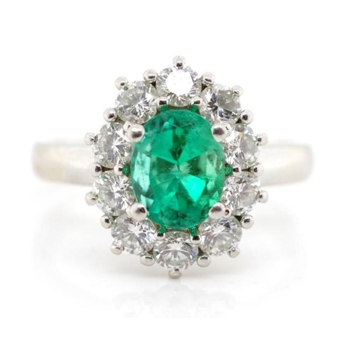 31 - Emerald and diamond set platinum cluster ring, marked PT. Approx 1x oval cut emerald 7.5mm x 5.98mm,...