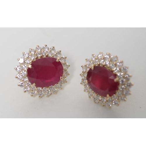 19 - Ruby, diamond and 18ct yellow gold earrings in a cluster stud setting. Approx 2x oval cut natural ru...