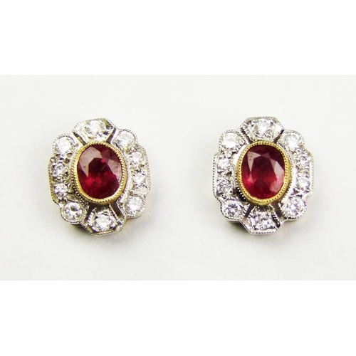 13 - A pair of ruby and diamond-set cluster ear studs, each with central oval ruby collet above a shaped ...