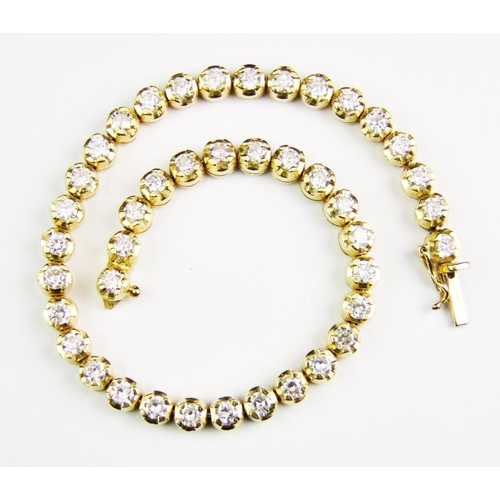 18 - A diamond-set 18 carat yellow gold 'tennis' bracelet, set with a total of forty-two brilliant-cut di...