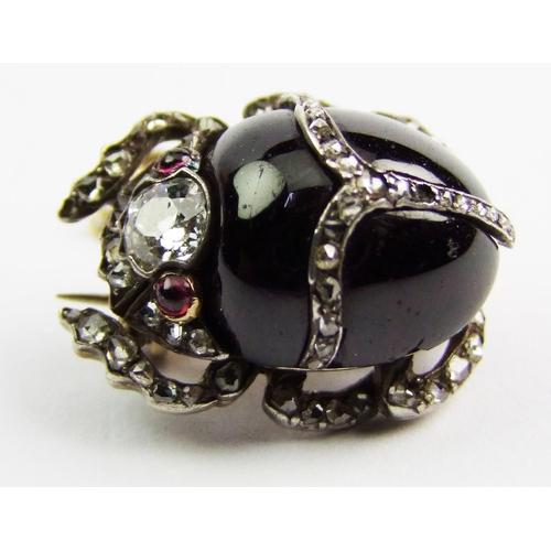 22 - A Victorian garnet and diamond-set beetle brooch, the cabochon garnet body with old brilliant-cut di...