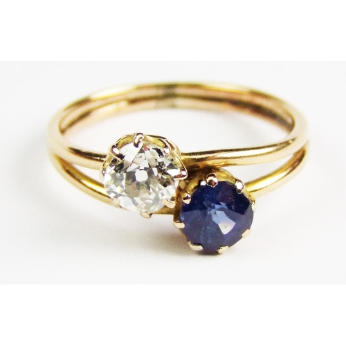 24 - A sapphire and diamond two stone ring, the old brilliant-cut diamond obliquely set to the circular-c...