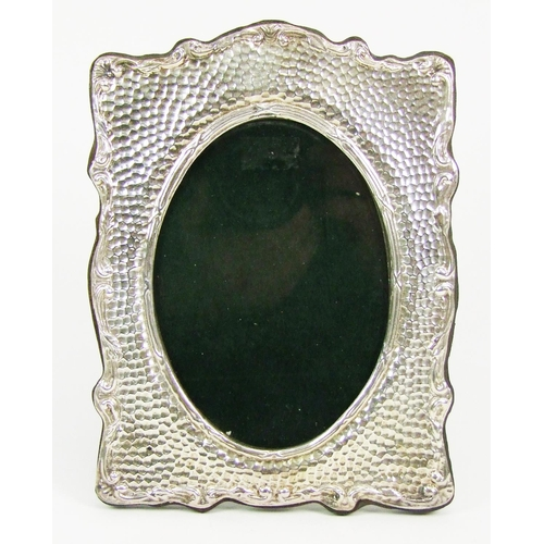 32 - A silver mounted easel photograph frame, with foliate scroll border and hammered decoration, oval op...
