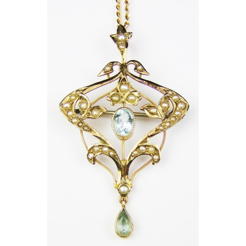 33 - An Edwardian aquamarine and seed pearl scroll design openwork pendant, stamped '9ct' to the reverse,...