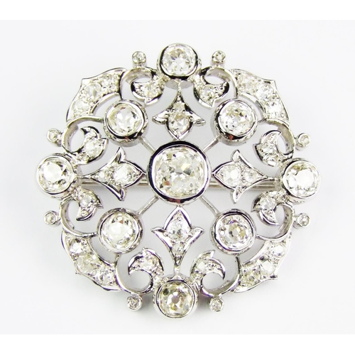 45 - A diamond-set  brooch, of openwork circular form, centrally-set with an old brilliant-cut diamond, w...