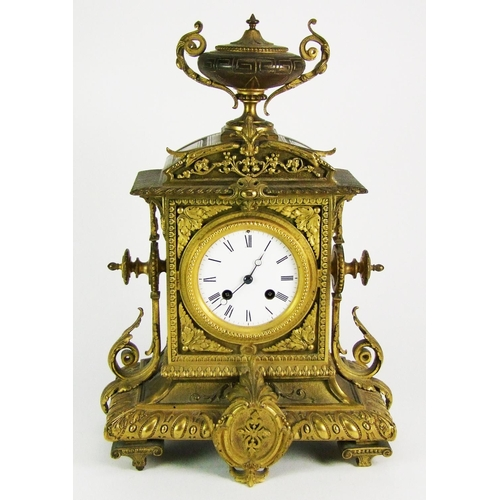 142 - A gilt brass mantel clock, with white enamel dial, the movement striking on a bell, the case surmoun...