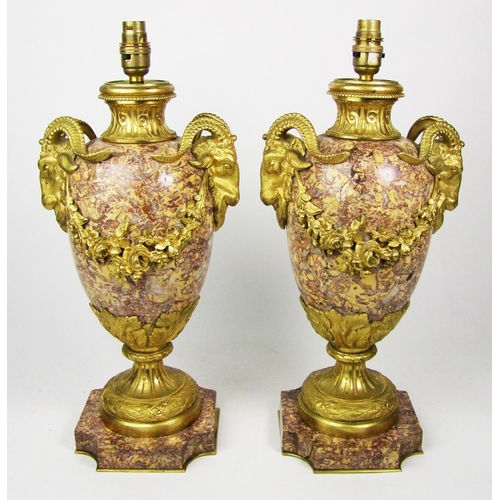 127 - A pair of marble and gilt metal table lamps, mounted with rams heads, and floral swags, acanthus ste...