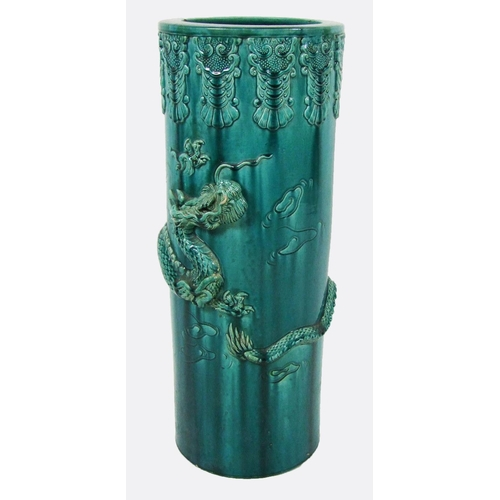 158 - A pottery umbrella stand, with a dragon in relief, height 61cm (24in.)....