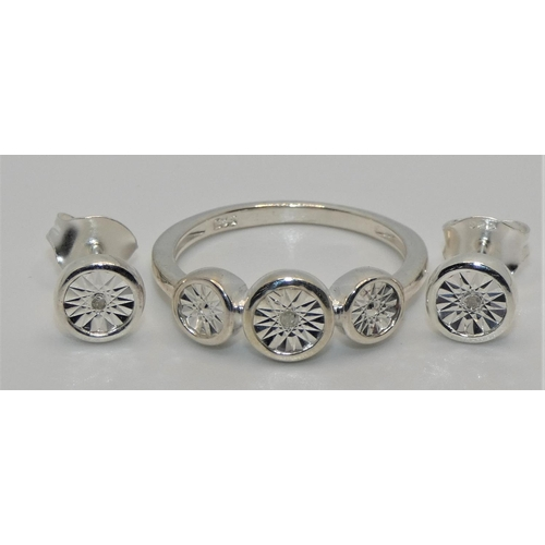 A silver and diamond set ring with matching earstuds.