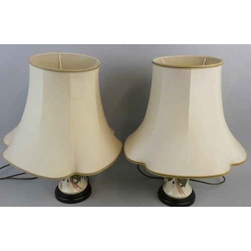 203 - A pair of Moorcroft floral pattern table lamps, in the '46/12' shape/type, pinks and greens on a cre...