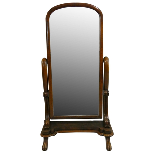 407 - A Victorian mahogany cheval mirror, the arched swivel mirror supported by scroll rams to a shaped ba...