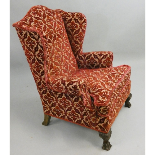 413 - An upholstered wing armchair, raised on hairy lions paw feet, 82 cm wide....
