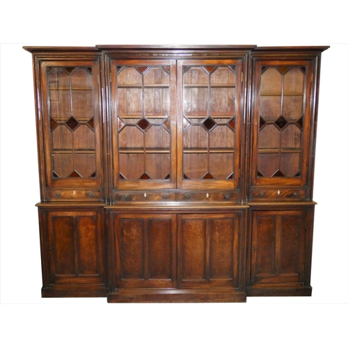 420 - A Georgian mahogany breakfront library bookcase, the stepped cornice above a pair of thirteen clear,...