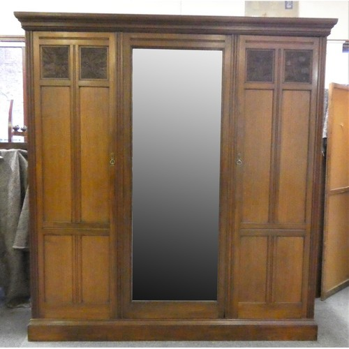A mahogany triple wardrobe with central mirrored door (pin attachment), the left side 'double' provides full width top shelf and lined 3/4 hanging space. The fitted right side provides top shelf, four slides over 3 graduated drawers, both side doors are paneled, the top ones being carved, 193 x 214 x 51 cm.