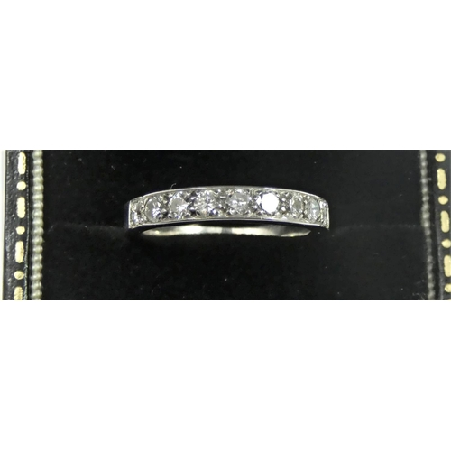 108 - A white metal, probably platinum and diamond half eternity ring, set with nine brilliant cut stones,...